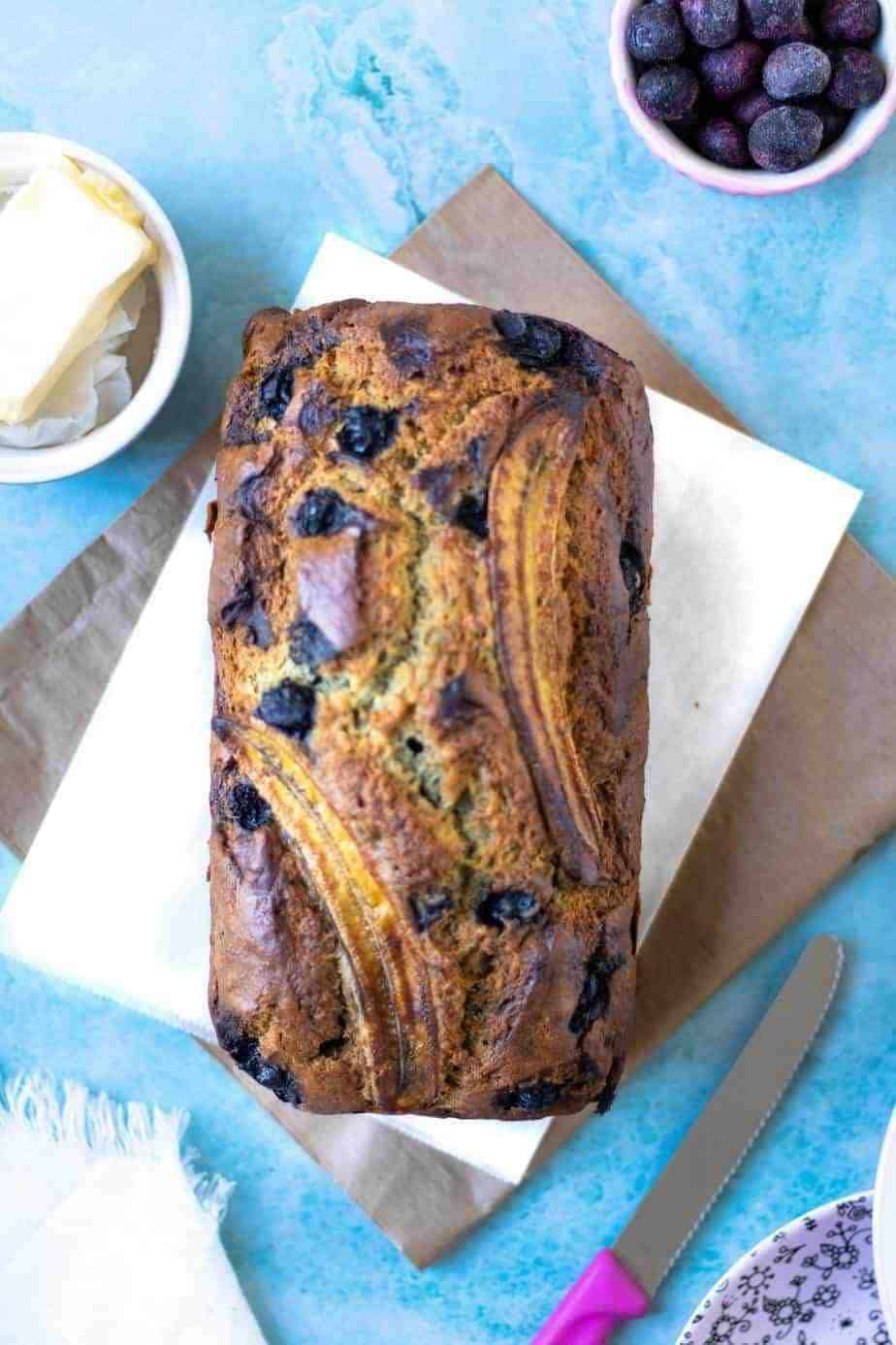 Banana Blueberry bread loaf on a piece of what parchment paper with a bowl of butter on the side and a bowl of frozen blueberries on the other side.