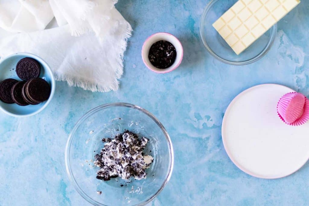 Ingredients in separate bowls, Oreos, white chocolate, Oreo crumbs.