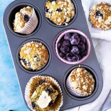 Blueberry Muffins with frozen blueberries and crumb topping in a muffin tin