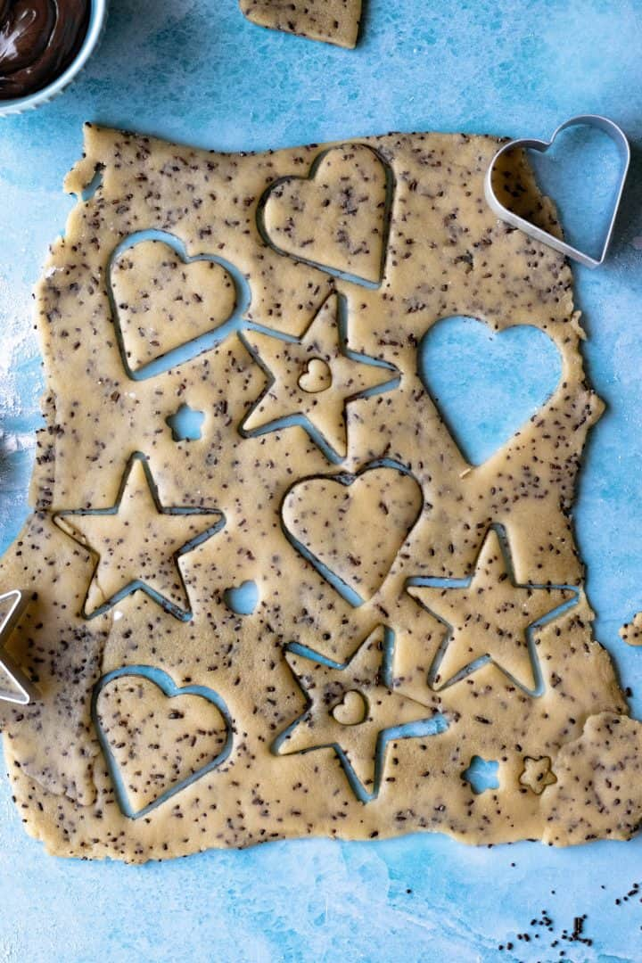 Rolled out Linzer cookie Dough with hearts and stars cut out.