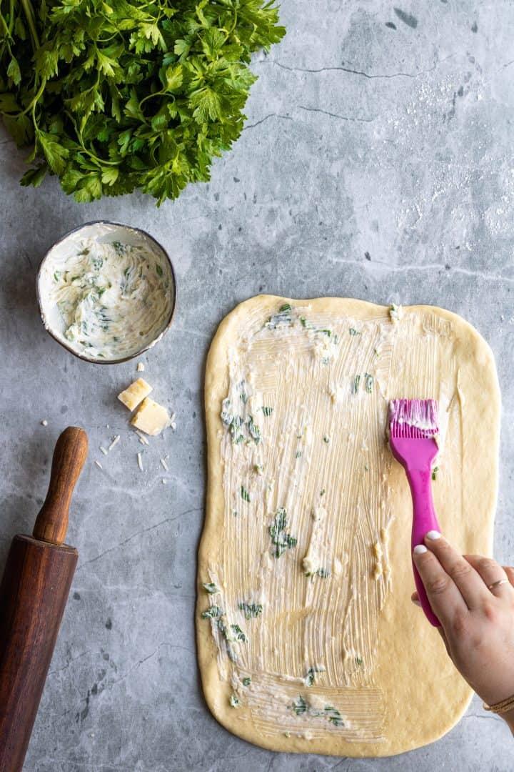 brushing garlic butter onto dough