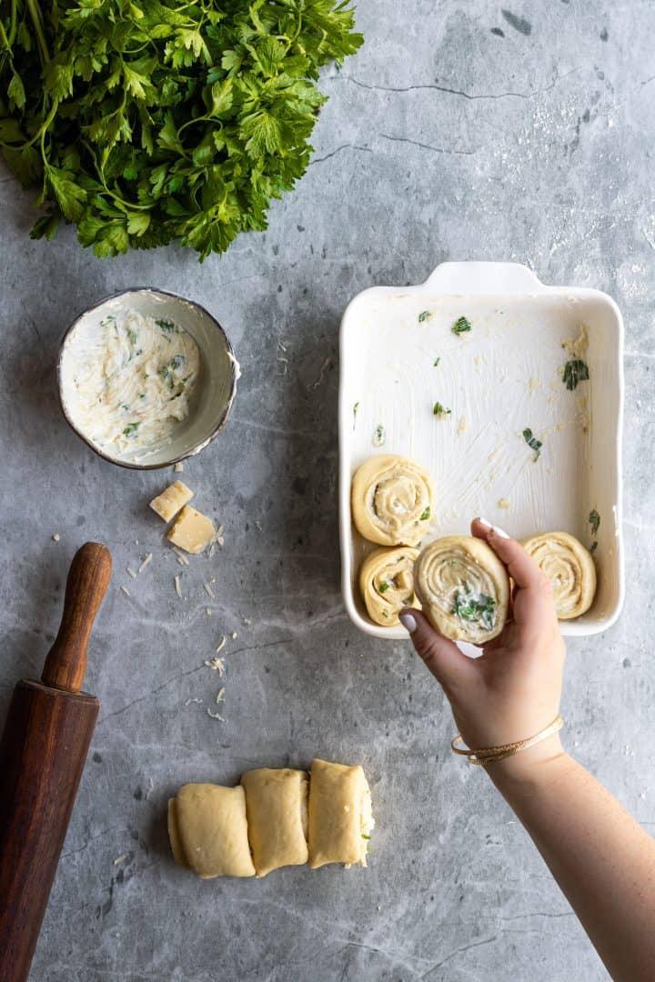 placing garlic rolls into baking dish